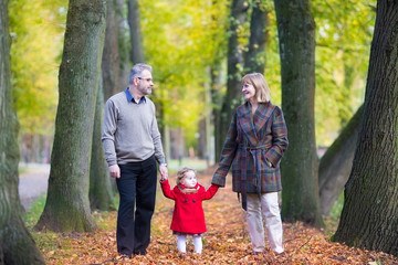 Happy couple walking in an autumn park with a toddler girl