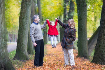 Couple playing with a little toddler girl in an autumn park