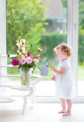Adorable curly baby girl in a white dress watering flowers