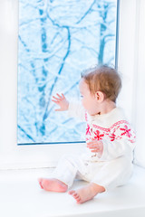 Baby in a sweater with Christmas ornament sitting at a window