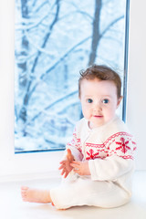 Funny little baby sitting next to a window to a garden with snow