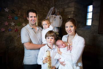 Happy young family with three children celebrating the baptism