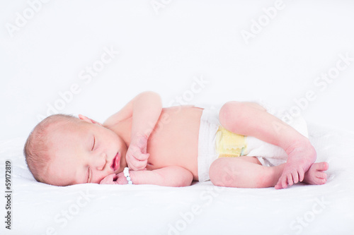 Sweet newborn baby sleeping on a white blanket