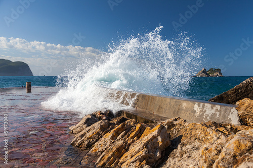 Stone breakwater with breaking waves. Adriatic Sea, Montenegro