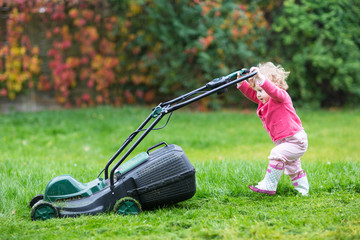 Baby girl in rain boots playing with a big green lawnmower