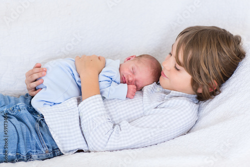 Newborn baby boy sleeping in the arms of his brother