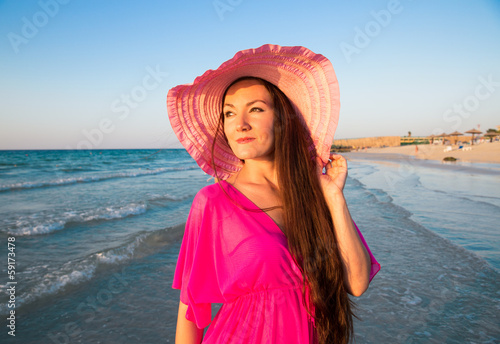 Portrait of attractive woman in hat with long hair on beach