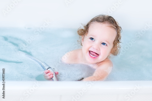 Beautiful little baby girl with big blue eyes playing in a bath