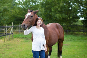 Attractive young pregnant woman and a horse standing in a field