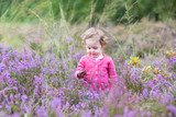 Cute little baby girl playing with purple heather flowers