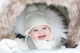 Laughing baby girl in a warm stroller wearing a winter jaket