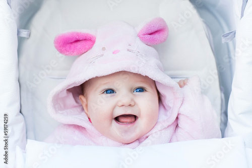 Cute laughing baby girl enjoying a stroller ride