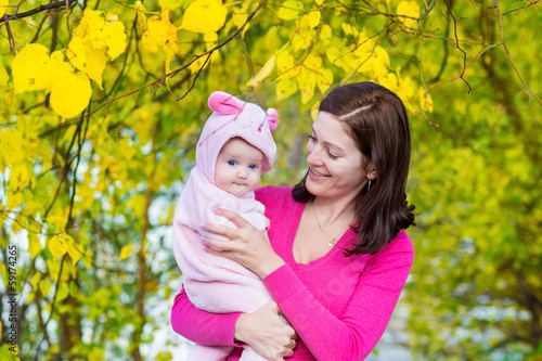 Leinwanddruck Bild Young mother and her baby daughter walking in an autumn park