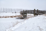 wooden bridge through frozen river in winter