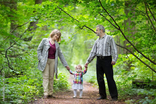 Young grandparents with their baby granddaughter in a park