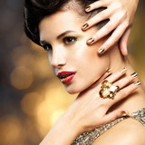 Fototapety Beautiful woman with gold nails and ring