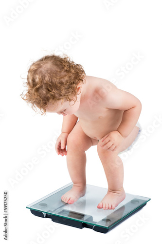 Very funny baby watching her weight, isolated on white