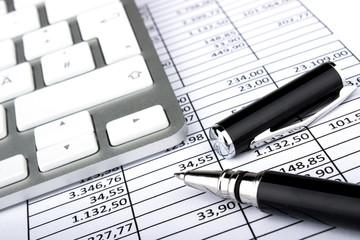 Kugelschreiber und Tastatur auf Tabelle