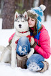 Happy woman playing with husky outdoors