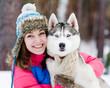 closeup teen girl embracing cute dog in winter park
