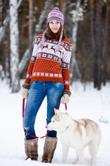 Girl with her cute dog in the winter forest