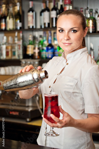 beautiful young barmaid making cocktail