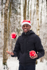Black man plays with red balls in the snow
