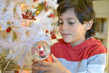 Boy holding Christmas glass ball