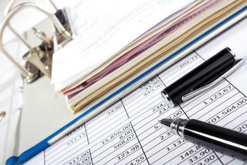 Kugelschreiber und Aktenordner auf Tabelle