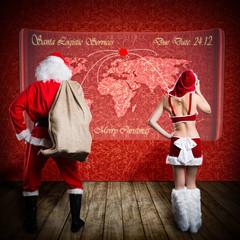 Santa und Miss Santa vor Weltkarte
