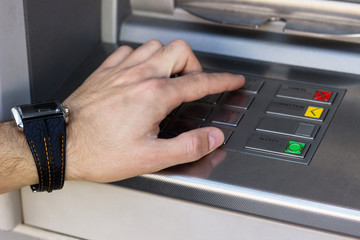 Hand entering personal identification number on ATM