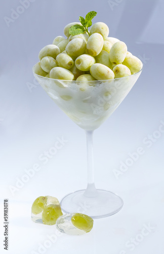Frozen grape in martini glass.
