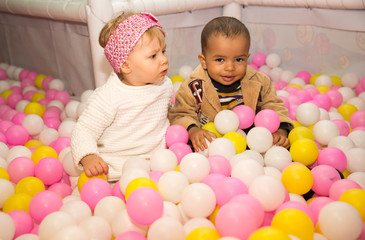 Happy children in colored ball on birthday on playground