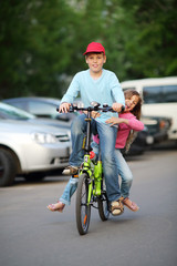 Happy brother and sister ride bicycle near car parking at summer