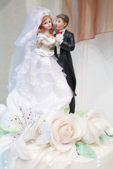 Figurines of bride and groom on wedding cake