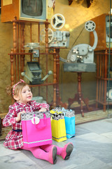 Little girl in pink sits on floor with bags near showcase