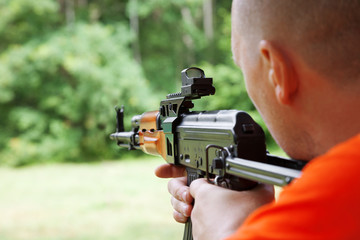 Man aiming at a target and shooting an automatic rifle for strik