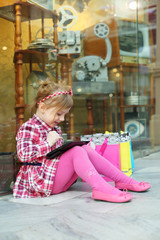 Little girl in pink sits on floor and looks at tablet pc