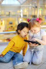 Little pretty girl and boy play with tablet pc on floor in mall.