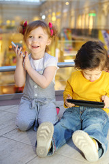 Little pretty girl with mobile phone and boy with tablet pc