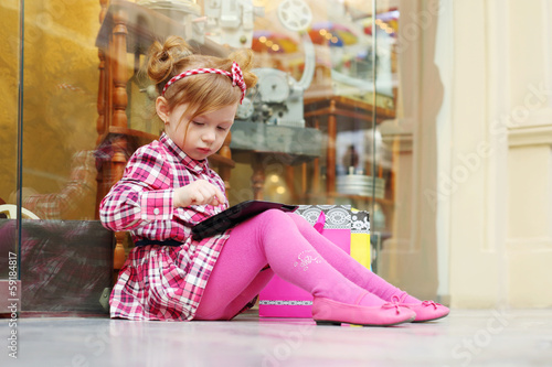 Little serious girl sits on floor and looks at tablet pc