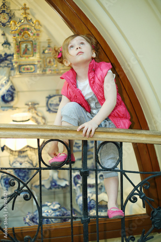 Little girl climbs onto railing and looks upward near showcase