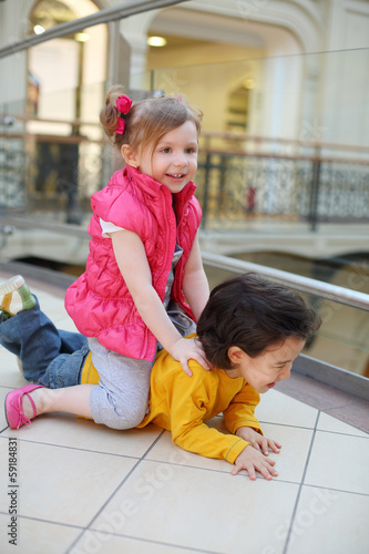 Little pretty girl and boy play on floor in big mall.