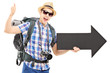 Tourist with backpack holding a big black arrow and giving thumb