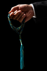 Hand Holding a Tasbih, a Muslim Rosary