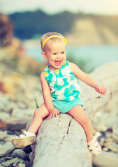 cheerful happy baby girl laughing on  walk in nature