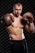 Guy with a boxing gloves showing muscles on fence background