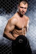 Powerful guy with a dumbbells showing muscles on fence backgroun