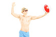 Young shirtless man playing with a beach ball