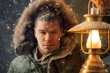 Brutal man walking under snowstorm at night lighting his way wit